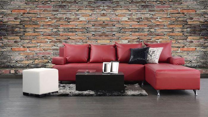 idée de canapé d angle couleur bordeau, revêtement sol et tapis gris, table basse noire, tabouret blanc, mur d accent en briques