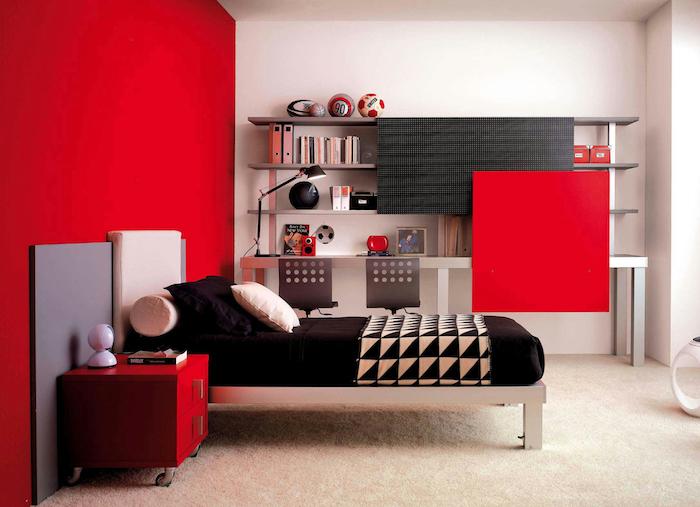 deco rouge et noir, mur d accent rouge et table de nuit avec tiroirs rouges, lit en inox, matelas et coussins noirs, étagère bibliothèque simple, tapis blanc