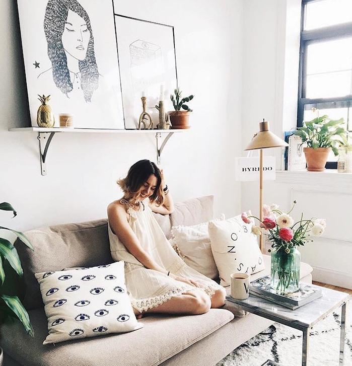 idee deco salon gris et blanc avec canapé gris, tapis blanc à motifs géométriques noirs, deco murale de dessins noir et blanc, coussins décoratifs, bouquet de fleurs,