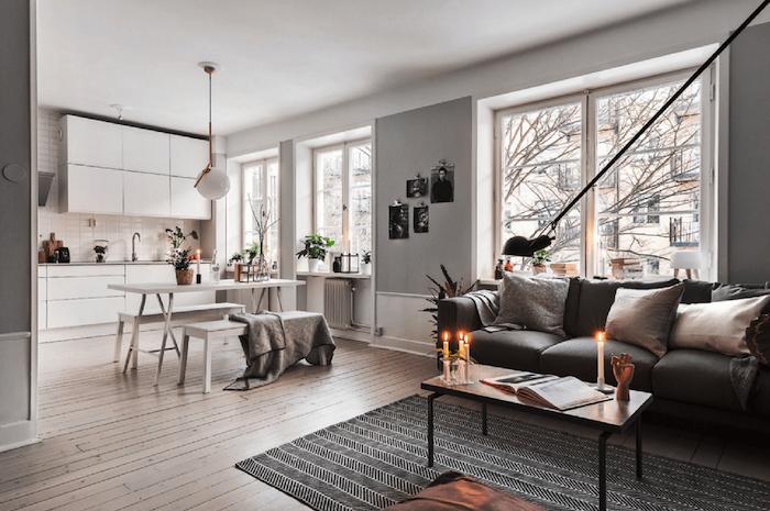 exemple de deco salon gris, avec canapé gris, tapis noir et blanc, table en bois et metal, parquet clair, façade cuisine, table et banc blancs, decoration de bougies