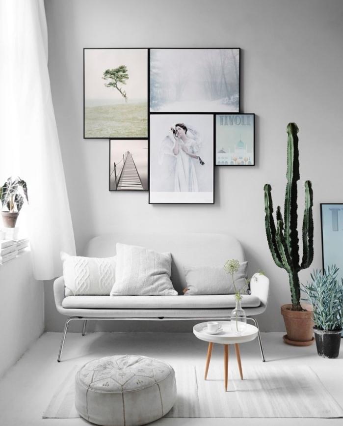 deco salon gris et blanc, canapé blanc, pouf et tapis gris, table basse minimaliste scandinave, deco murale de cadres, peinture et photos, cactus et autres plantes