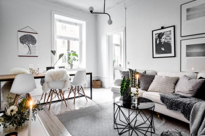 deco salon gris et blanc, abec canapé blanc cassé, coussins gris, noir et blanc, table basse noire design, table en bois et métal et chaises scandinaves, jeté de fourrure