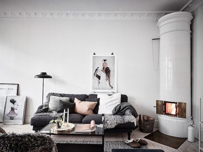 idee deco cocooning, tendance hygge, canapé gris anthraccite avec des coussins, gris, noir et blanc, jeté de fourrure gris, table basse noire, cheminée blanche