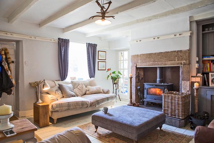 deco salon gris et blanc, murs couleur blanche, canapé gris, coussins decoratifs, table basse grise, tapis oriental, cheminée noire, panier de rangement en rotin
