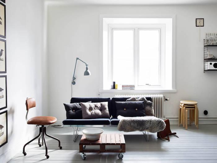 revêtement sol et murs blancs, canapé gris anthracite, table basse en palette à roulettes, jeté de fourrure, chaise en cuir marron
