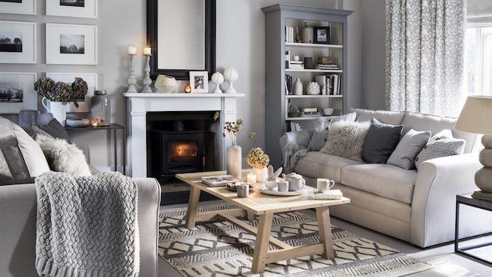 modele deco salon gris et blanc, canapés blancs, cheminée vlanche, tapis gris et blanc, table basse bois rustique, plaid tricoté gris, bibliothèque et deco murale de photos noir et blanc