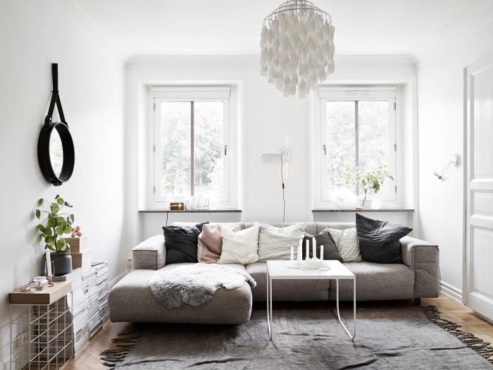 deco salon gris et blanc, canapé et tapis gris, coussins, gris, blanc et rose, jeté de fourrure grise, suspension originale, pile de livres, petit miroir rond