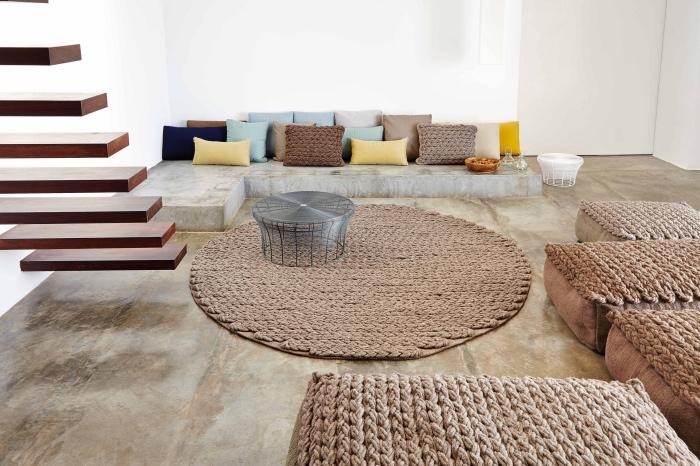 idée de deco salon moderne, sol couleur beige et mur couleur blanche, tapis et assises marron ethnique, escalier flottant, canapé béton par sol, coussins colorés