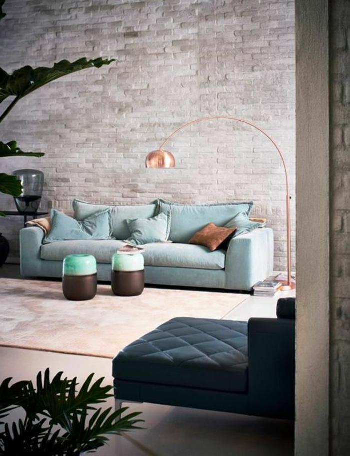 deco salon moderne, mur en briques style industriel, sofa bleu, tapis rose pâle