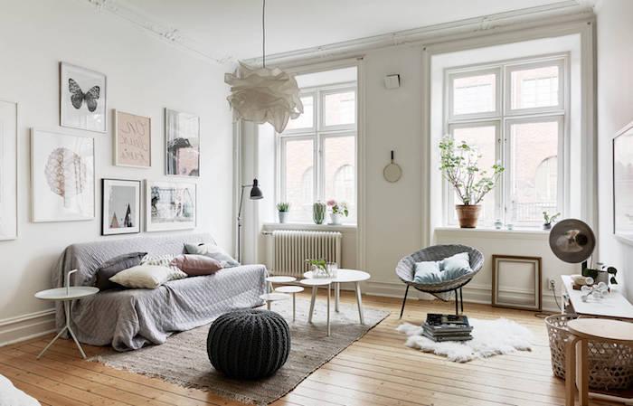 idee deco scandinave dans un salon à coussin cocooning, canapé avec couverture grise, tapis gris, tables basses blanches, parquet clair, chaise en rotin et metal, deco murale art romantique