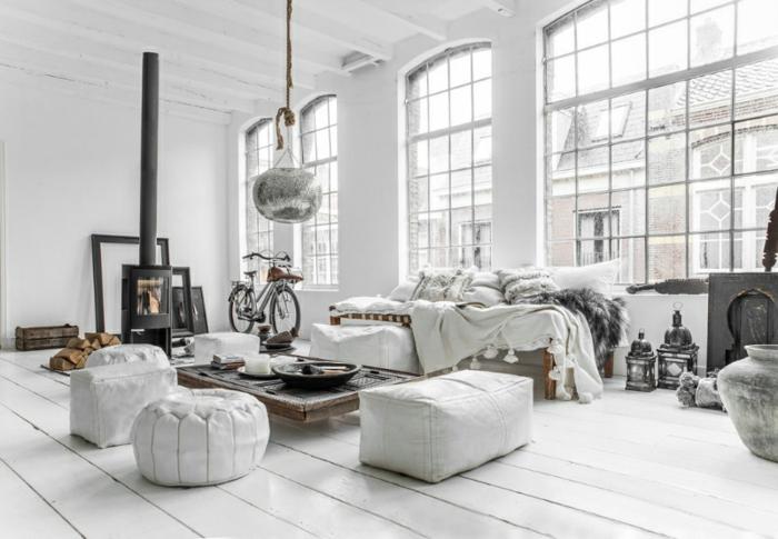 déco scandinave dans un salon en blanc, parquet blanc, canapé blanc avec peau grise, table basse design intéressant, poufs gris, parquet blanchi, cheminée, suspension originale, lanternes decoratifs