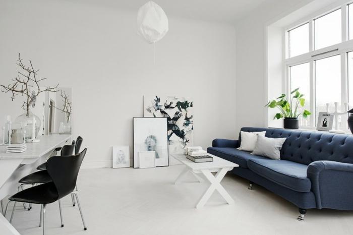 idée déco scandinave, décor tout en blanc avec un canapé bleu foncé contrastant, revêtement sol et murs blanc, table basse blanche, deco dessins graphiques, accessoires scandinaves