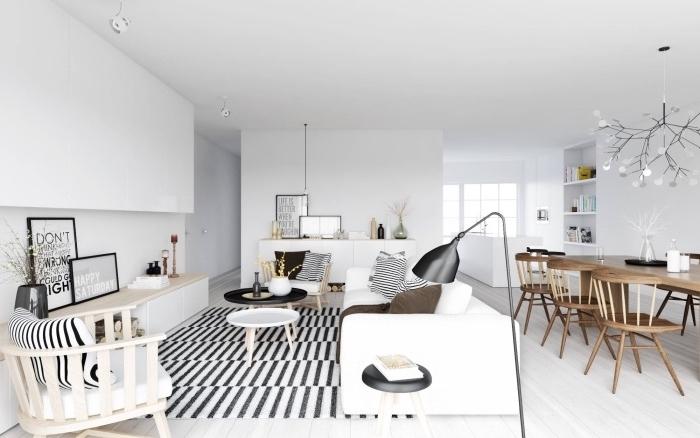 amenagement salon scandinave ouvert sur salle à manger, tapis noir et blanc, canapé blanc, chaises en bois, parquet clair, salle à manger chaises et table en bois