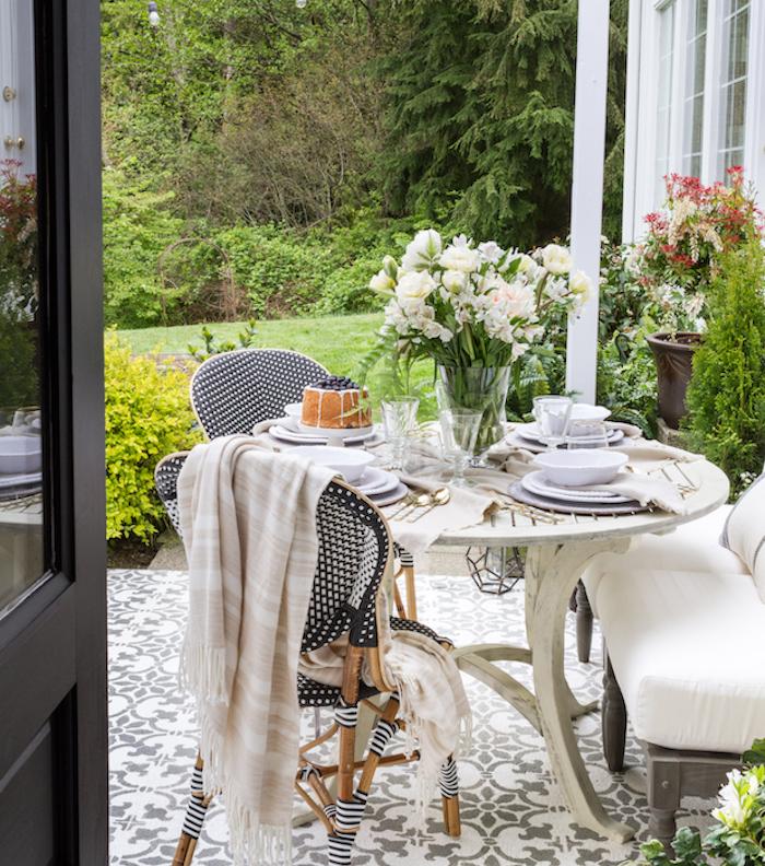 une petite salle à manger sur une terrasse zen, revêtement carrelage mosaique blanc et gris, table blanche, canapé bois avec coussin d assise blanc, chaises en bois, tissu blanc et noir