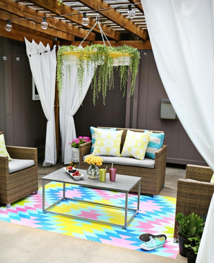 amenagement terrasse exterieure, idee salon de jardin tressé, fauteuils et canapé en rotin, tapis multicolore, table basse, suspension fleurie, pergola en bois