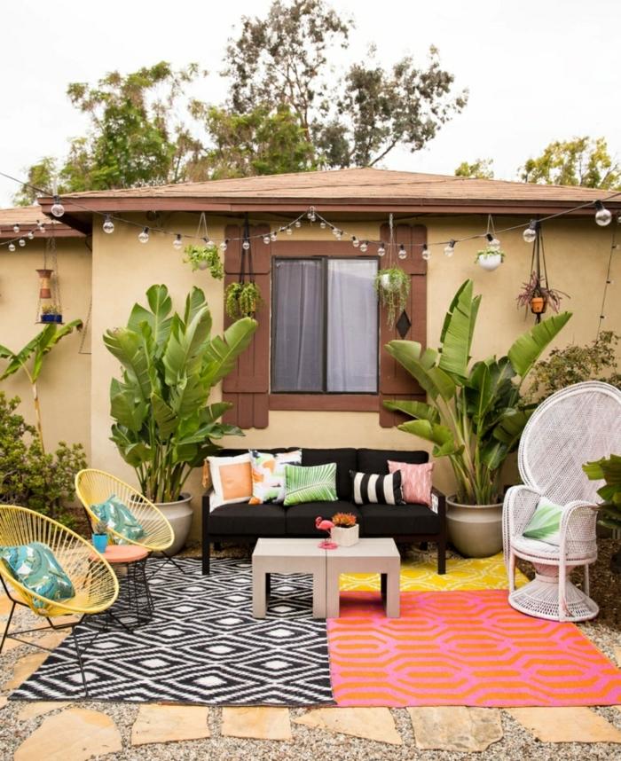 amenagement terrasse exterieure, style zen bohème, guirlande lumineuse, tapis noir et blanc, rouge, jaune, fauteuil blanc, chaises jaunes, canapé noir, plantes vertes