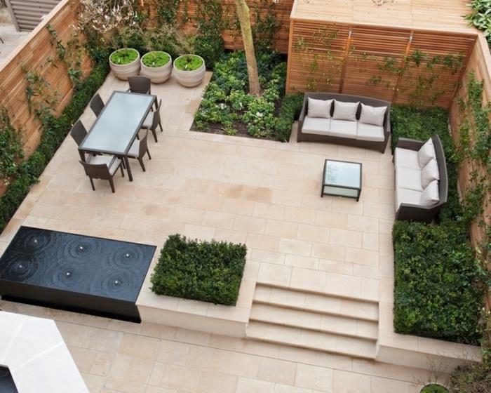 deco terrasse avec carrelage, canapés en rotin, salle à manger chaises marron et table longue, fontaine originale, pots de fleurs, arbustes et plantes grimpantes