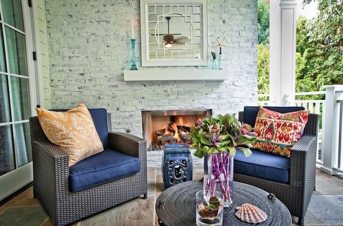 deco terrasse zen avec revêtement carrelage, fauteuils tressés, coussins d assise bleus, table basse design, coussins orientaux, cheminée exterieure, mur de briques blanchies