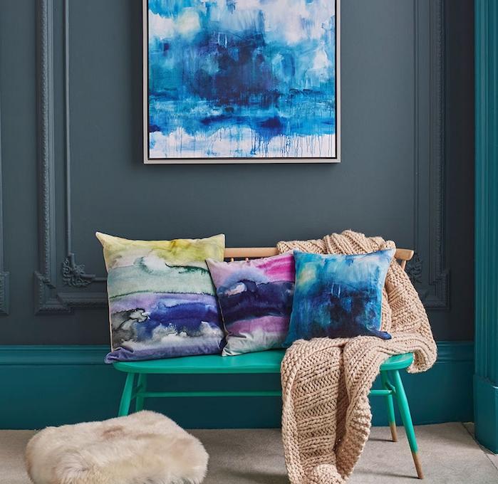 decor deco cocooning, banc metallique verte, coussins vert, jaune, bleu, rose, plaid tricotée, tapis gris, mur gris anthracite, tabouret avec revêtement en peau animal
