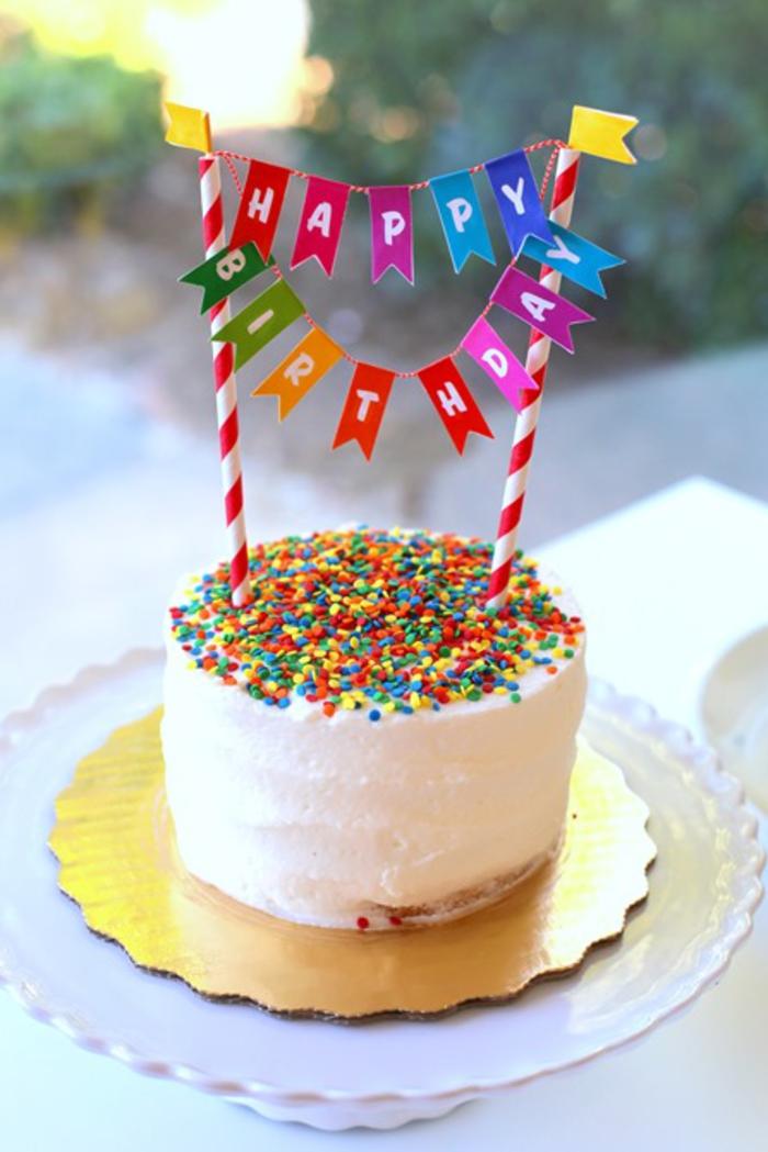 une décoration anniversaire colorée, gâteau d'anniversaire génoise moelleux recouvert de glaçage au crème et décoré de vermicelles et de petite guirlande de fanions