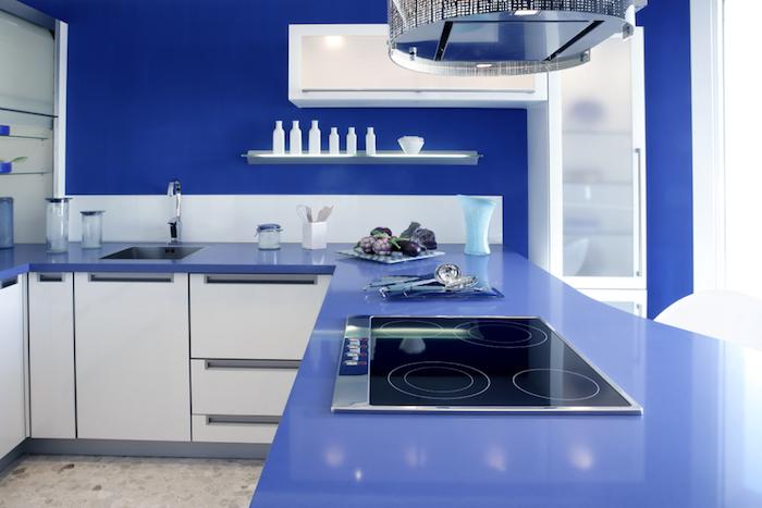 cuisine aménagée, comptoir en bleu foncé avec meubles en blanc, étagère murale avec éclairage led