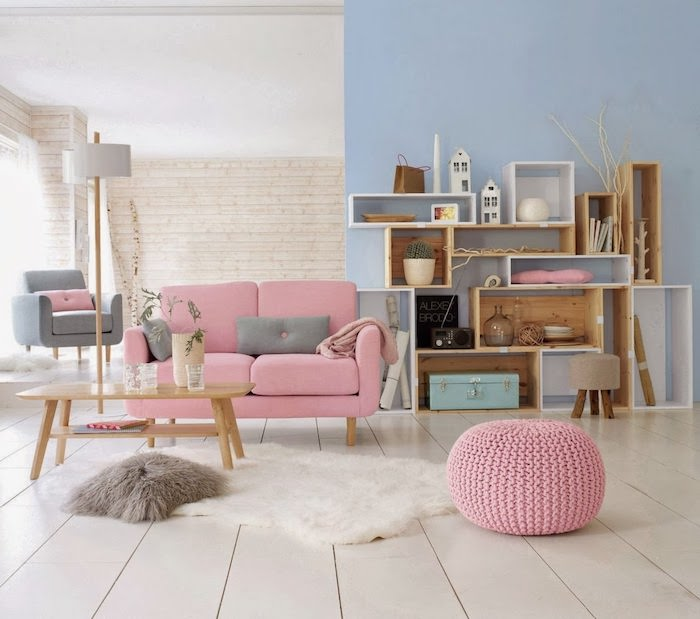 salon aux murs bleus et blancs, tapis moelleux blanc et coussin en faux fur marron, petite table de salon basse en bois
