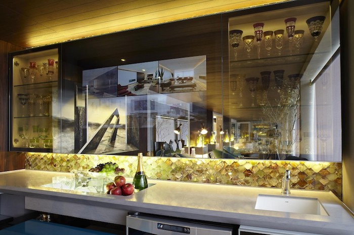 meuble bas, plafond en bois avec éclairage jaune, armoires de cuisine en verre, comptoir en marbre avec évier carré