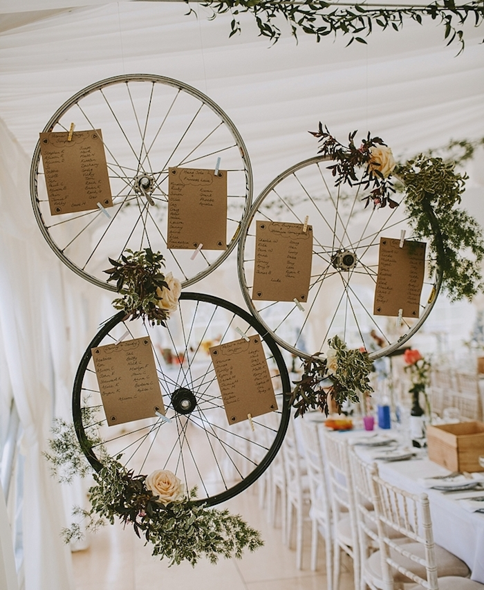decoration mariage champetre chic, plan de table original en roues de vélo avec deco florale, branches vertes, roses