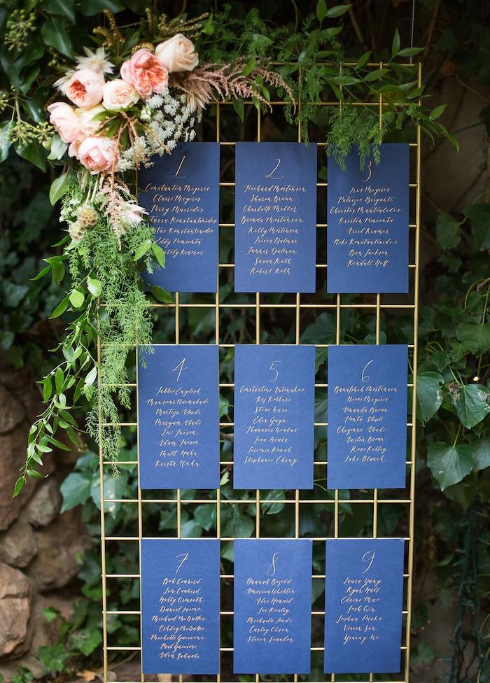 plan de table original en grille dorée avec des petits bouts de papier, listes invités fond noir et lettres dorées, décoration bouquet de fleurs