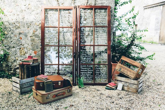 idee deco mariage, plan de table original en portes avec encadrement en bois marron et des carreaux en verre avec les noms des invités écrits au feutre blanc, deco cagette bois, malle vintage e bouquins