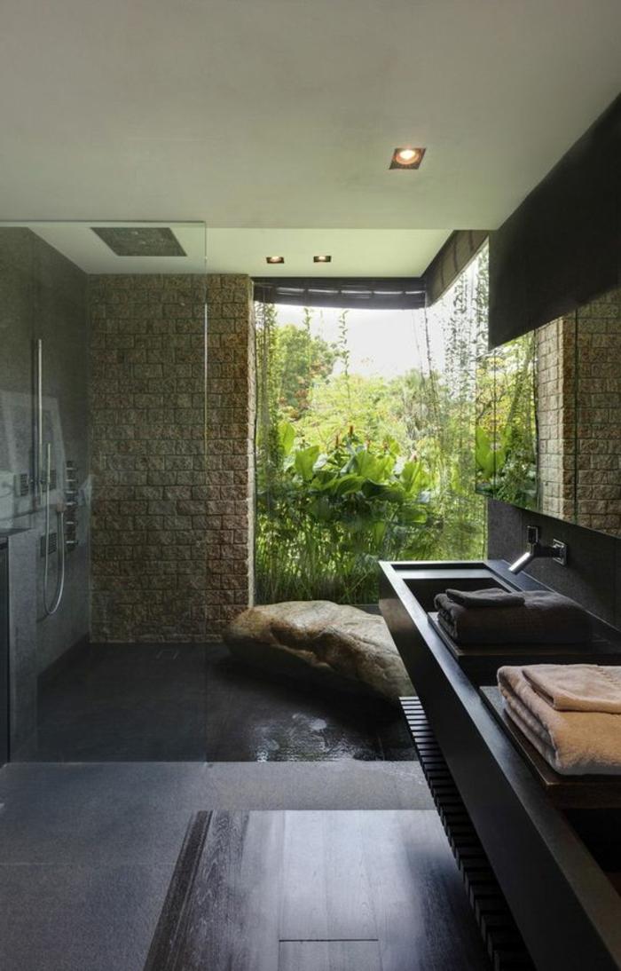 décoration salle de bain, murs en pierren sol en béton noirn douche plain pied