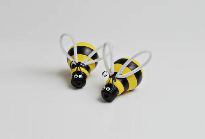 des abeilles fabriquées à partir d ampoules électriques, décorées de bandes noires et jaunes, des yeux mobiles et ails, déco avec de la récup
