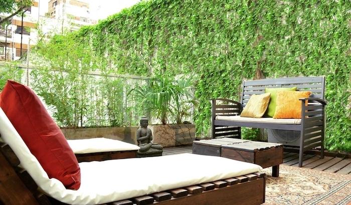 terrasse zen en bois avec chaise longues en bois, matelas blanc, coussins rouges, tapis oriental, table et canapé en bois, statuette de bouddha, plante grimpante, statuette bouddha