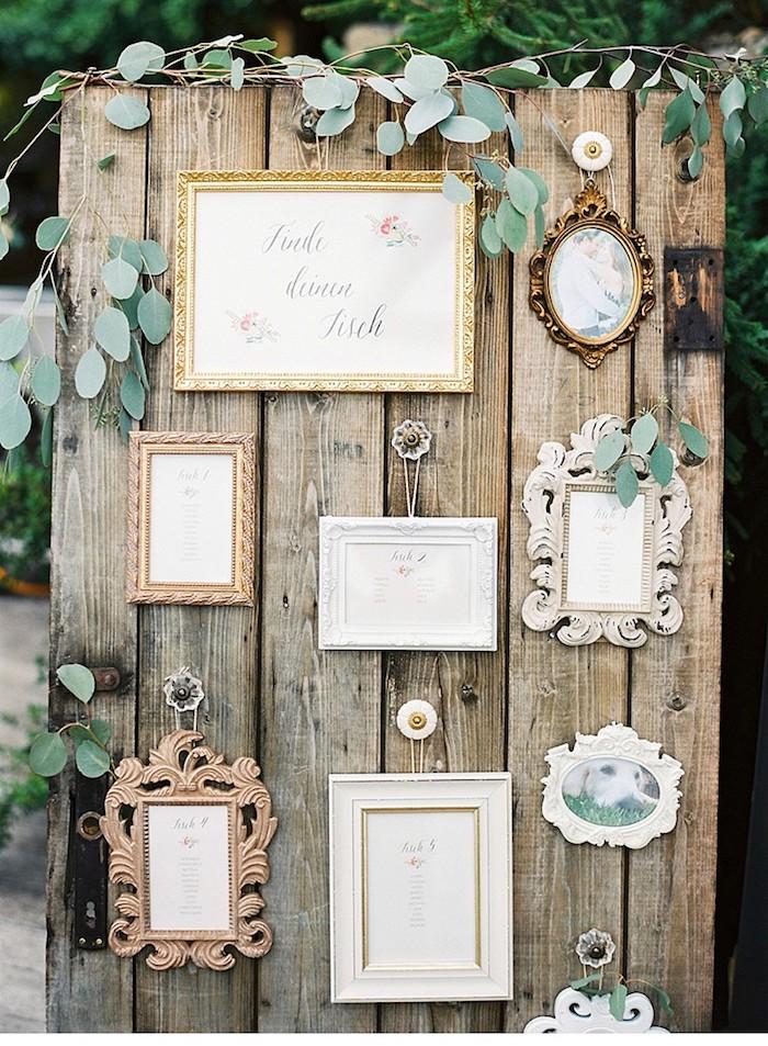 plan de table mariage en plein air, des planches de bois brut assemblées et cadres photo vintage avec prénoms invités, petite décoration verte