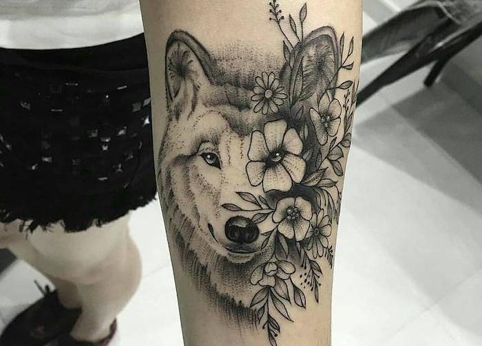tatouage loup femme, tête de loup avec fleurs sur le bras, dessin en encre modèle feminin