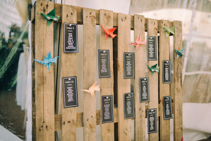 listes invités noires, lettres blancs sur une palette bois rustique et papier origami coloré, idée plan de table mariage original