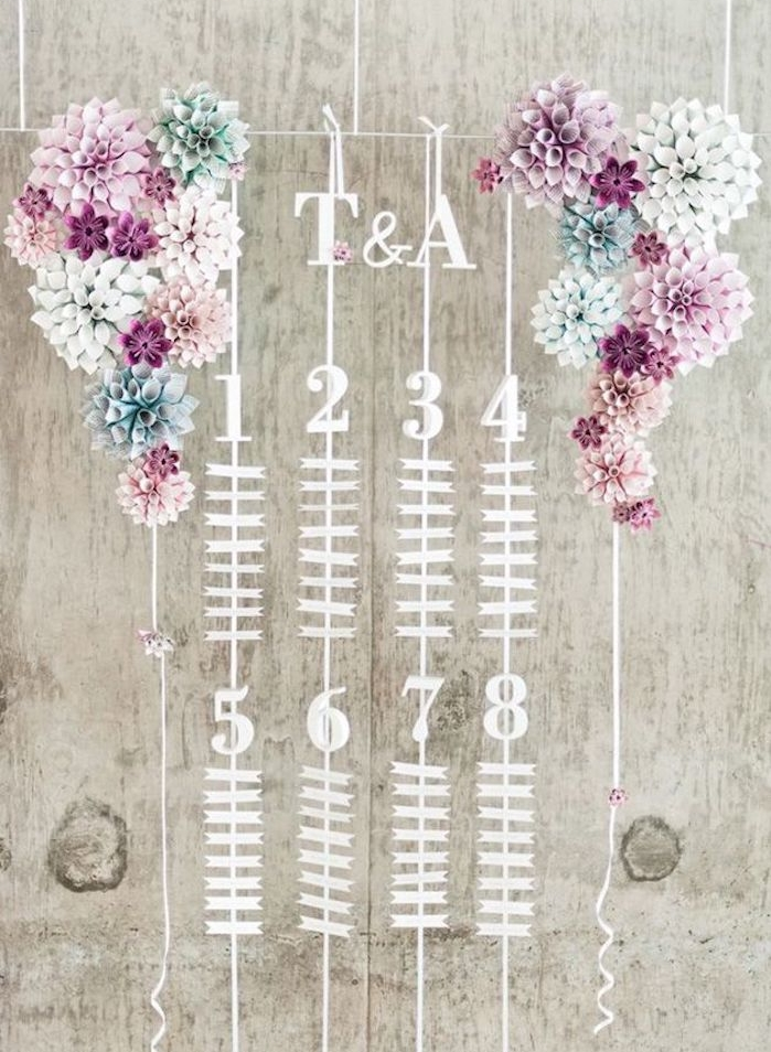 plan de table pour mariage, petites étiquettes avec les noms des invités et décoration de fleurs en papier coloré des deux côté