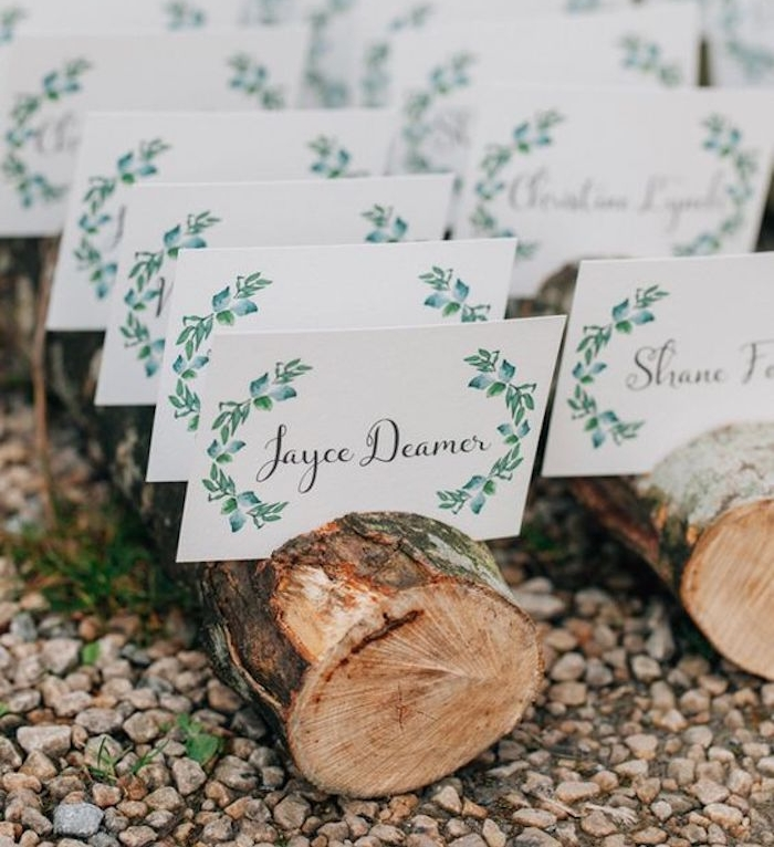 plan de table mariage en bûches de bois, façon rustique avec des étiquettes prénom, nom invité et dessin laurier