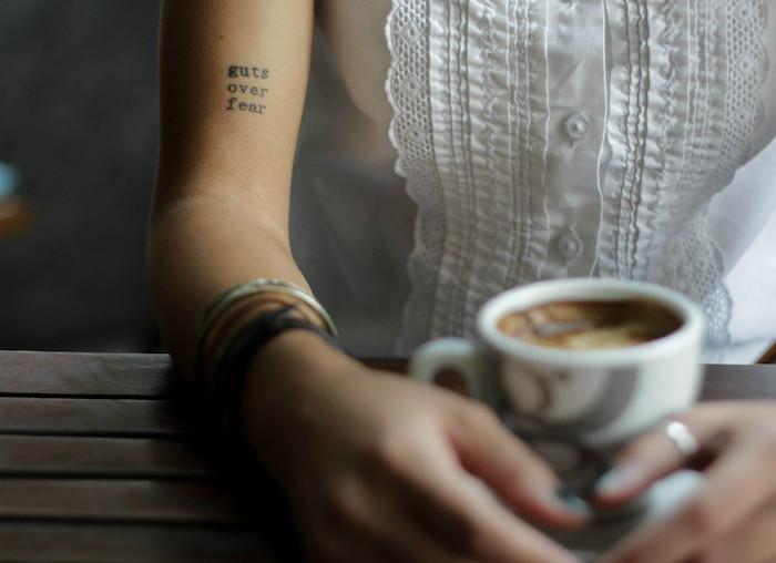 tatouage phrase, manucure noire sur ongles courts, chemise blanche sans manches avec boutons et décoration en dentelle