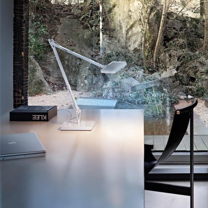 lampe design blanche sur un bureau scandinave avec chaise noire, idée de grande fenêtre donnant sur un paysage charmant