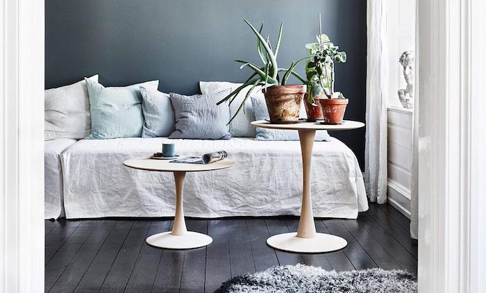 tapis cocooning en fusse fourrure, canapé avec couverture blanche, coussins gris, bleu et blanc, tables en bois, pots de fleurs vertes