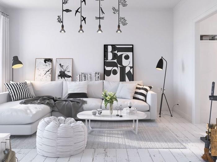 idée comment décorer un salon scandinave, tapis gris, canapé blanc avec coussins décoratifs noir et blanc, panneaux décoratifs graphiques, suspensions originales
