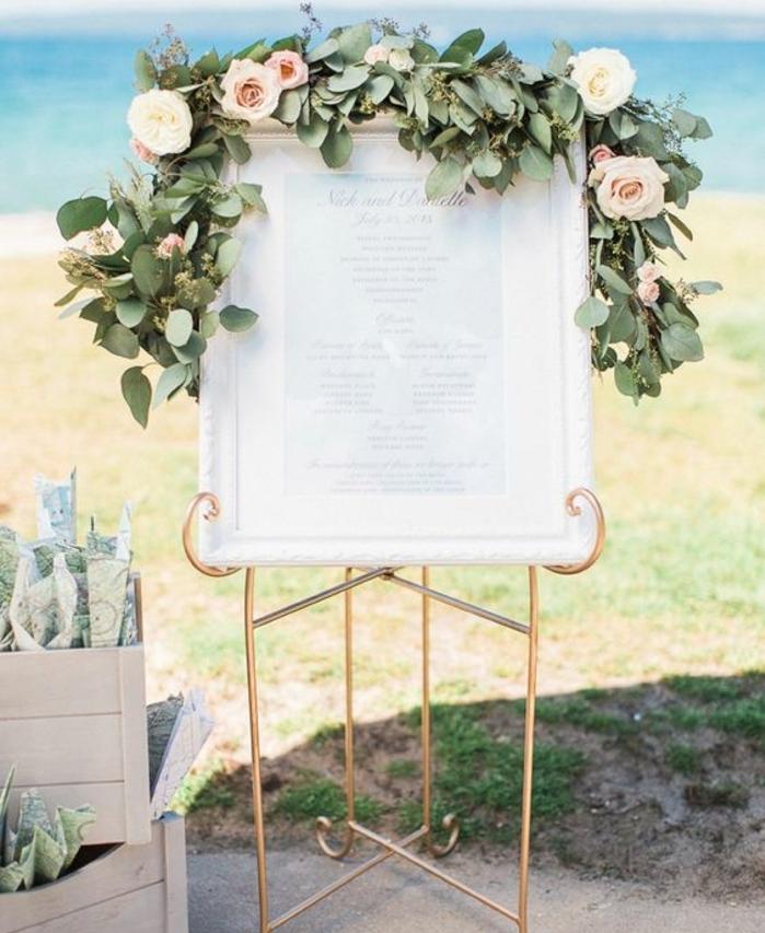 plan de table mariage a imprimer, liste simple imprimée dans un cadre blanc, support doré et guirlande verte avec des roses