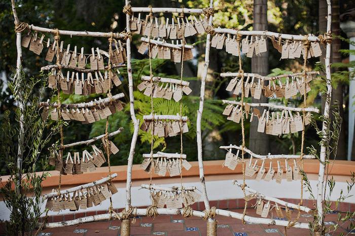 modele de plan de table mariage en bois flotté, branches de bois transformée en petite échelle avec étiquettes en papier kraft pour écrire le nom des invités