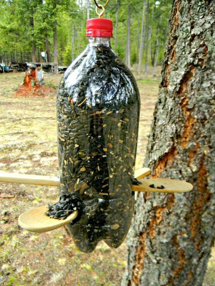 fabriquer mangeoire oiseaux bouteille plastique, cuillères en bois et bouteille de soda pleine des graines de tournesol