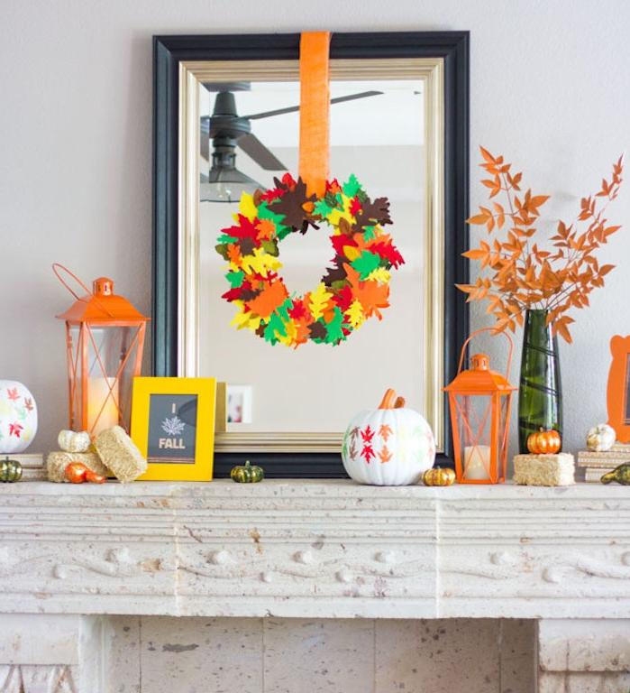 une couronne de feuilles mortes en mousse, suspendues à un ruban orange, lanternes et citrouille décorative, deco automne a faire soi meme sur une cheminée