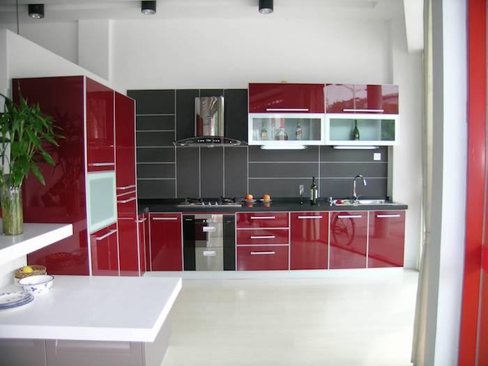 façade cuisine rouge bordeau avec crédence grise, aspirateur inox, petit ilot gris avec plan de travail blanc, sol blanc cassé