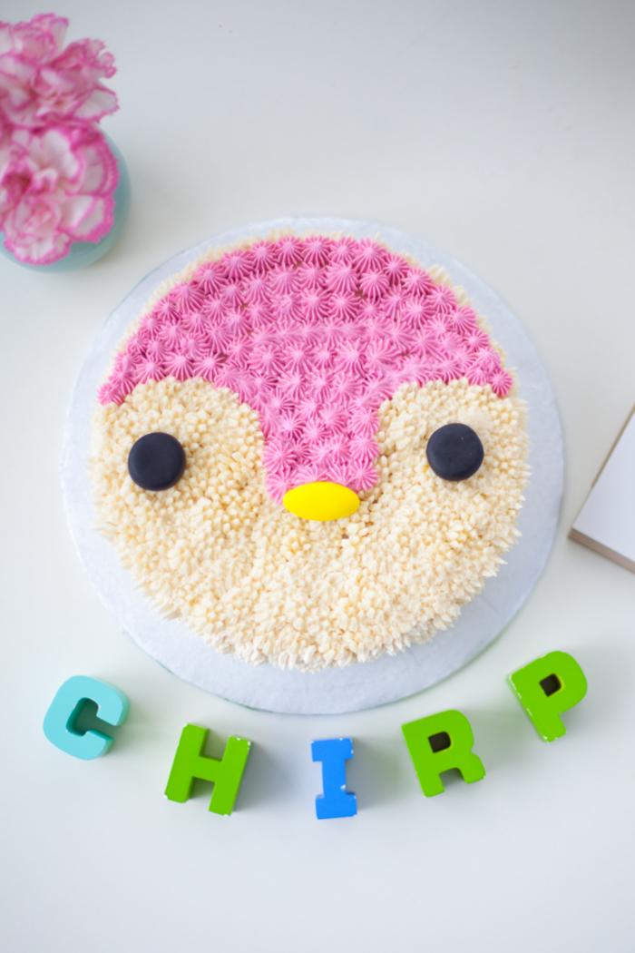 une décoration de gâteau originale et facile à réaliser avec une poche à douille, un gateau anniversaire 1 an fille en forme de têtê de pingouin
