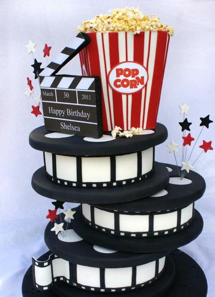 gateau d'anniversaire aux motifs de cinéma avec boite de pop corn géante au dessus