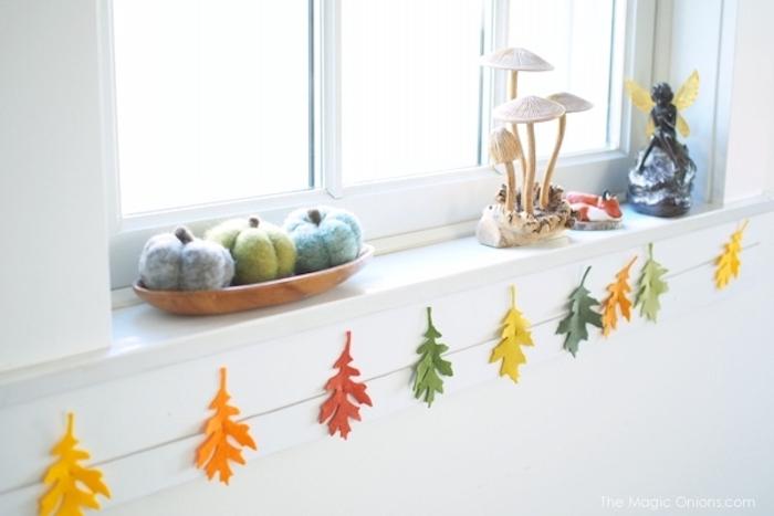 une guirlande de feuilles mortes colorées en feutrine sous une fenêtre, petites citrouilles en tissu, deco automne a faire soi meme